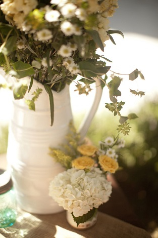 Using white pitchers as flower vases gives an organic feel to your wedding day décor.
