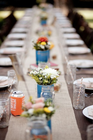 A little country mixed with a little modern…a burlap table runner, mixed with mason jars, antique canned vases, and your personal guest favors of aluminum can coolers.
