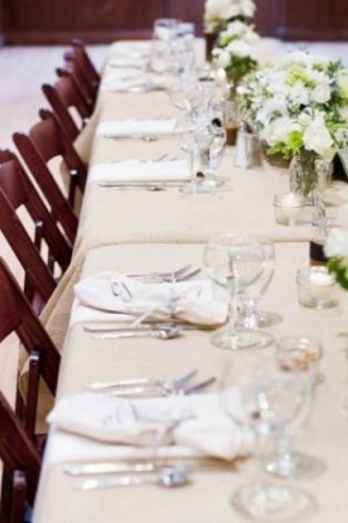 """An extended option of going """"country"""" is to use one of our burlap table cloths paired with simple touches of class by way of tea lights and mason jar flower arrangements."""